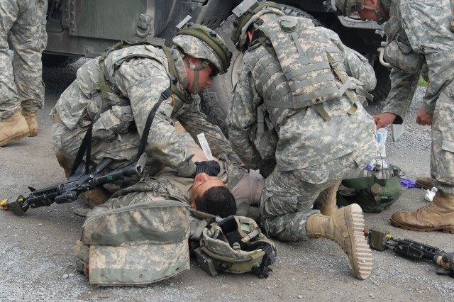 FORT DRUM, N.Y. (June 12, 2009) - Responding quickly to a casualty, Soldiers from the 22nd Battalion 22nd Infantry treat the chest wound while others set up a perimeter in response to a roadside attack during Operation Courage Peak, the battalion training exercise.