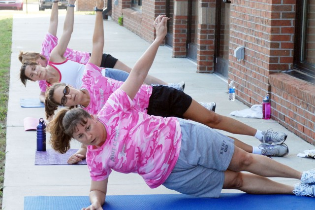 Alisha Shultze, Catherine Mangrum, Jennifer Magsig and Breta Sandifer do a side plank exercise in a boot camp class Tuesday at Smith Fitness Center.