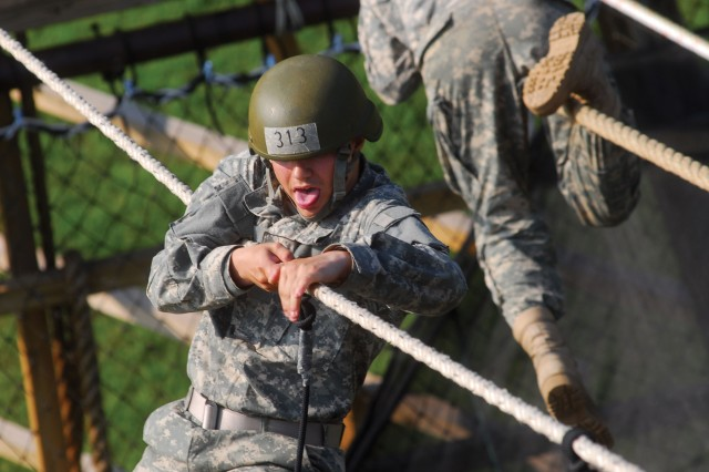 Two rope Bridge 2.jpg: PVT Jonathan Fishbeck concentrates on crossing a two-rope bridge. The bridge consists of one rope to walk on and one rope located at chest level to balance.