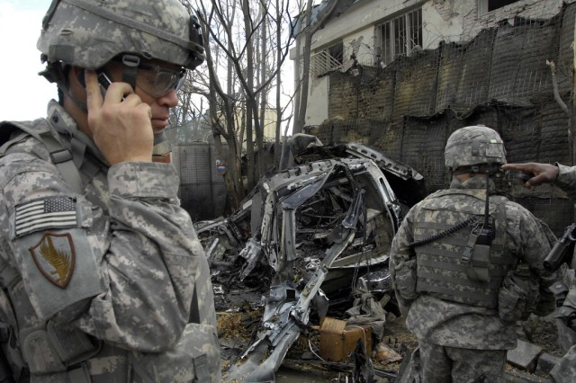 Members of the force protection team at Camp Eggers, Afghanistan, assess damage resulting from an explosion near the gate. A vehicle-born improvised explosive device exploded near the German Embassy and a U.S. base. Eliminating threats such as the VBIED is the focus of Army's 3rd Counter-IED Conference scheduled, July 28-30, in Charlottesville, Va.