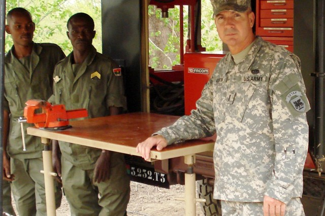 Chief Warrant Officer Randy Austin stands in front of a maintenance trailer with Burkina Faso soldiers during a peacekeeping exercise in June. Nearly 1,300 troops from various African nations attended exercise JIGUI, a multinational exercise conducted by the Economic Community of West African States (ECOWAS) standby force. The exercise focused on the logistical capabilities necessary to support the ECOWAS standby force in peace support operations.