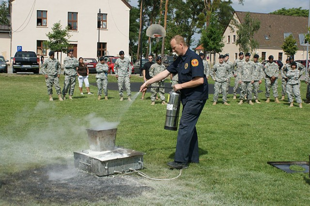 Mannheim Fire Inspector Thomas Rothmann demonstrates how to focus the nozzle of a fire extinguisher for maximum effectiveness during Fire Prevention training June 25 in Mannheim, Germany, held as part of Installation Management Command-Europe's Fire Prevention Campaign.