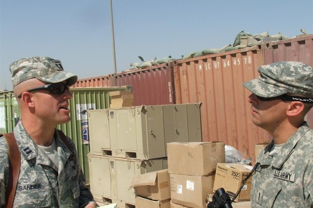U.S. Air Force Capt. Michael J. Sander discusses with U.S. Army 1st Lt. Felipe T. Barrera the container inventory and progress of the Mobile Redistribution Team at Joint Security Station Loyalty, Iraq, June 1.