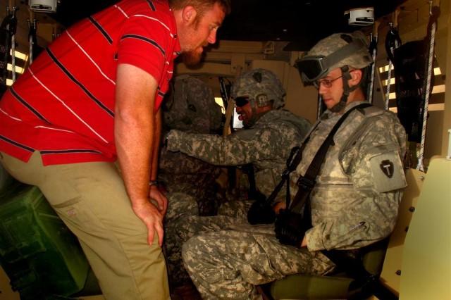 287th Sust. Bde. MET trainer Randy Kerschner instructs a Soldier on the proper use of his seatbelt prior to a rollover exercise, May 29.