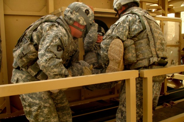 Soldiers from Alpha Battery, 3rd Battalion, 133rd Field Artillery, practice the extracting an injured Soldier from the MET Trainer's gunner's hole, May 29.