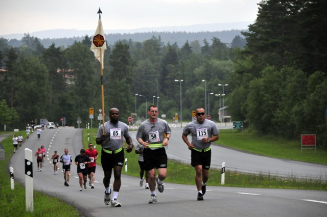 Soldiers representing the U.S. Army Garrison Grafenwoehr carry the unit guidon as they charge the first hill during the Army Europe 10-Miler in Grafenwoehr, Germany, June 27.