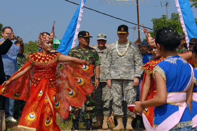 Lt. Gen. Benjamin R. Mixon, commander, U.S. Army Pacific and Tentara Nasional Indonesia- Angkatan Laut, or Indonesian Navy Vice Admiral Y. Didik Heru Purnomo, the head of general staff for the Indonesian Armed Forces, are escorted by dancers to a ceremony marking the opening of a  newly build baby care clinic in a village approximately 30 minutes from Bandung, Indonesia, June 28. The ceremony marked the completion of three Humanitarian and Civic Assistance projects, which are part of Garuda Shield 2009. The projects were a joint effort between engineers from the Tentara Nasional Indonesia-Ankatan Darat, or Indonesian Army, and engineers assigned to the Utah National Guard.