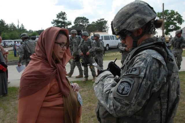 A Soldier from the 108th Military Police Company takes down medical information from a pregnant evacuee prior to departure during a noncombatant evacuation operation conducted by the 2nd Brigade Combat Team, 82nd Airborne Division at Camp Mackall, N.C. June 24-26. The exercise tested the unit's capability to deploy on short notice to help evacuate American citizens and others trapped in a war-torn foreign country.