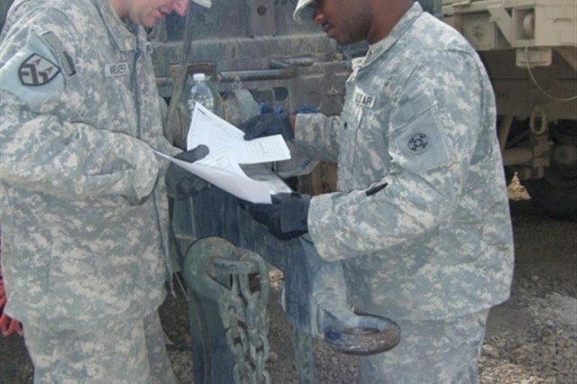 Spc. Michael Weaver, a native of Portage, Ind., and Spc. Roman Woods, a South Bend, Ind. native, both Soldiers with the 855th Quartermaster Company conduct an inventory of their equipment at Camp Liberty, Iraq June 12.