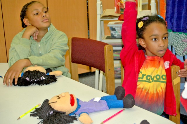 Six-year-old Morgan Jordan waits her turn to answer questions as 10-year-old Nazarene Valerio looks on during the The Edge! puppet workshop session at the Wiesbaden Library.