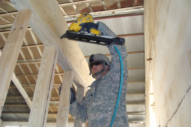 BAGHDAD - Spc. Dale Webb, carpentry/masonry specialist from Ashland, Ohio, 46th Engineer Combat Battalion (Heavy), 225th Engineer Brigade, uses a nail gun to secure a top plate on the Joint Operations Center at Joint Security Station Shield.