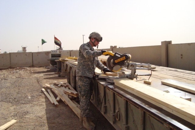 BAGHDAD - Spc. Robert Shoults, carpentry/masonry specialist from Berkeley, Mo., 46th Engineer Combat Battalion (Heavy), 225th Engineer Brigade, uses a miter saw while constructing the Joint Operations Center at Joint Security Station Shield. Since the Security Agreement calls for closing of smaller combat outposts and joint security stations throughout Baghdad, engineers have been diligently working to create work and living spaces outside the city.