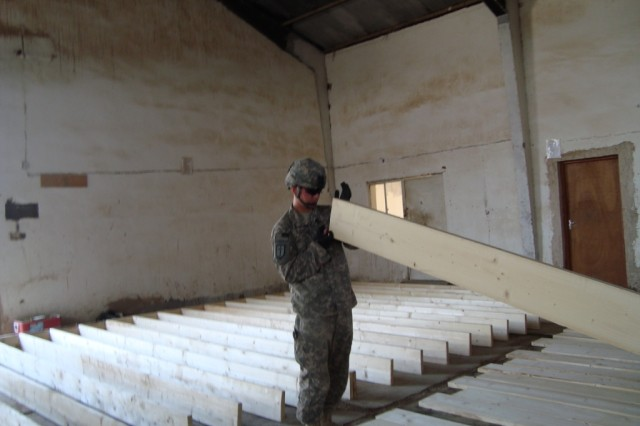 BAGHDAD - Sgt. Thomas Keller, carpentry/masonry team leader from Witney Point, NY, 46th Engineer Combat Battalion (Heavy), inspects the crown on boards that will make up the floor joist for the Joint Operations Center at Joint Security Station Shield. Joint facilities such as these are critical as the Iraqi Security Forces take the lead in securing peace and stability in Baghdad.   The construction project should be completed June 19.