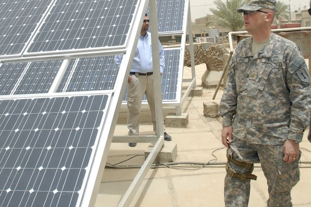 BAGHDAD - Maj. Andrew Attar, a native of Bristol, Conn., joint project management officer, 2nd Heavy Brigade Combat Team, 1st Infantry Division, Multi-National Division - Baghdad, inspects the newly installed solar panels on the roof of the Dahkel Clinic in the Hurriyah neighborhood of northwest Baghdad June 17.  As the main health clinic in Hurriyah, the solar panels will keep the clinic powered longer, providing more service to 500,000 Iraqis.