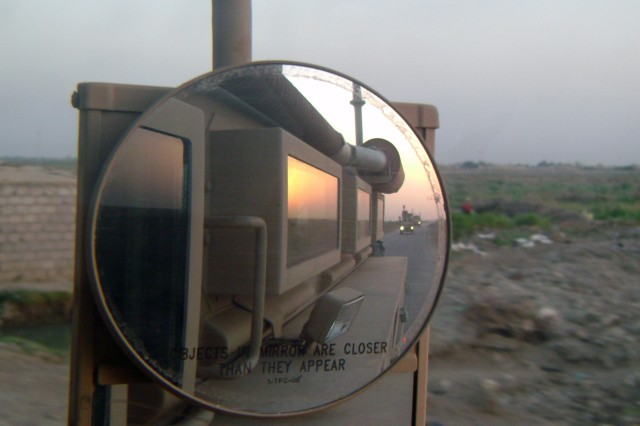 """BAGHDAD -As seen from the rearview mirror, the 515th Engineer Company (Sapper), attached to the 225th Engineer Brigade, moves through the Maysan province conducting route clearance operations. The 515th Eng. Co. cleared 84,854 kilometers of road on more than 688 missions during their 15 month deployment which took them on route clearance missions in nine of the 18 provinces in Iraq.  """"We just went where route clearance was needed the most,"""" said Capt. Andrew Hutchinson, executive officer of the 515th from Kate, Texas."""