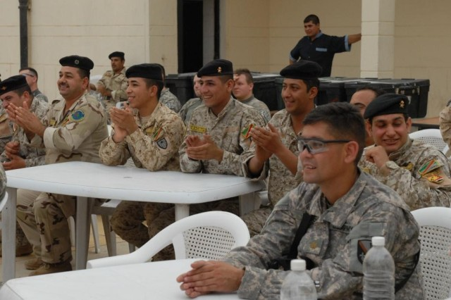 BAGHDAD - Maj. Andy Magee (foreground right), Pineville, La., 225th Engineer Brigade, and Iraqi Army engineer Soldiers enjoy dancing entertainment provided at the first ever Iraqi Engineer Sapper Call, June 17, at the 6th Iraqi Army engineer headquarters at al-Muthana in central Baghdad. The Iraqi engineer staff provided authentic Iraqi food and to games that strengthen partnership efforts.