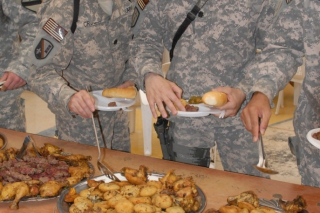 BAGHDAD - Lt. Col. Jerry Crooks (left), deputy commander 225th Eng. Bde. and Lt. Col. Matt Zajac (right), commander 46th Engineer Combat Battalion (Heavy), serve themselves authentic Iraqi food at the inaugural Iraqi Engineer Sapper Call, June 17, at the 6th Iraqi Army engineer headquarters  at al-Muthana in central Baghdad. The effort is a way for engineer Soldiers to come together and enjoy food, music, dancing, and fun while strengthening partnership ties.