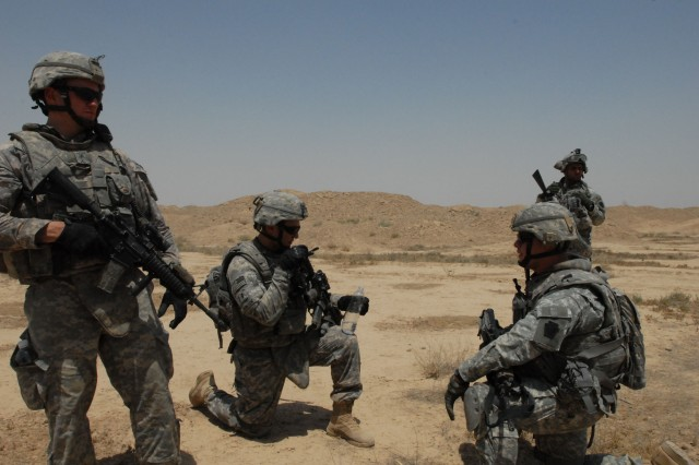 NUBAI, Iraq - Staff Sgt. Christopher Lohr (left) of Springfield, Pa., 1st Lt. Eric Ponzek (kneeling, center) of Collegeville, Pa. and Capt. John Mance (kneeling, right) of Norristown, Pa., commander of Headquarters and Headquarters Company, 1st Battalion, 111th Infantry Regiment, 56th Stryker Brigade Combat Team, discuss their next move during a search for weapons caches near Nubai, north of Baghdad, June 16.