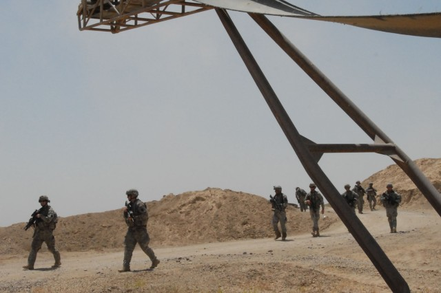 NUBAI, Iraq - Soldiers from Headquarters and Headquarters Company, 1st Battalion, 111th Infantry Regiment, and 856th Engineer Company, 56th Stryker Brigade Combat Team, enter a quarry near Nubai, north of Baghdad, June 16 during a search for weapons caches.