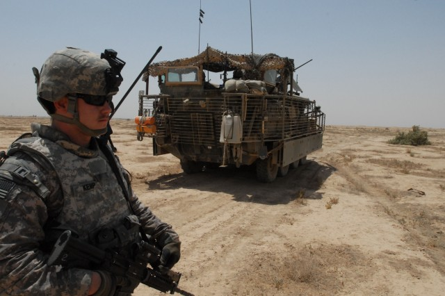 NUBAI, Iraq - Spc. Jake Kemp of Phoenix, Ariz., with Headquarters and Headquarters Company, 1st Battalion, 111th Infantry Regiment, pulls security in the desert near Nubai, north of Baghdad, during a search for weapons caches June 16. Kemp joined the 56th Stryker Brigade Combat Team's deployment to Iraq through an inter-state transfer from the Arizona National Guard.