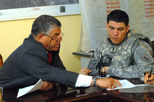 """BAGHDAD -- First Lt. Justin Casey, a native of Ogdensburg, N.Y., and contracting officer representative assigned to Special Troops Battalion, 2nd Brigade Combat Team, 1st Infantry Division and Dr. Ibrahim Al-Nedawi read the contract for the asphalt and road paving equipment operator apprenticeship program in Nasir Wa Salam, here, June 16.  """"The new road project not only improves the infrastructure but it provides jobs to the Sons of Iraq,"""" said Casey."""