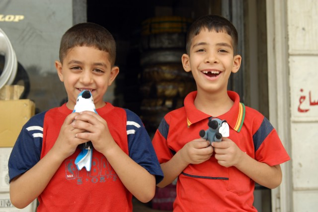 """BAGHDAD - Two Iraqi boys smile after receiving stuffed animals from Iraqi Police in the Ameriyah neighborhood during a joint patrol with the IP and Soldiers of the 463rd Military Police Company, 93rd Military Police Battalion, 8th Military Police Brigade, here, June 17. The stuffed animals were donated to deployed Soldiers to be distributed to Iraqi children. """"It helps with the perception that the IPs are good, they are here to help,"""" said Staff Sgt. Preston O'Neal, a military policeman from Dixon, Mo. """"The locals get the sense that the IPs care."""""""