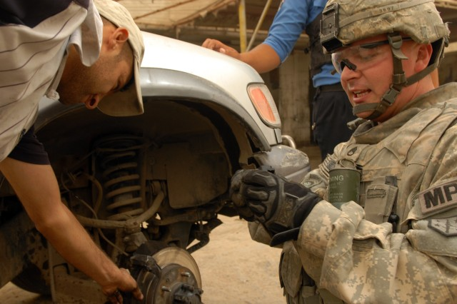 BAGHDAD - Staff Sgt. Preston O'Neal, a military policeman assigned to 463rd Military Police Company, 93rd Military Police Battalion, 8th Military Police Brigade, takes time to use his mechanical skills to help an Iraqi identify a problem with the brakes on his car during a joint patrol with the IP in the Ameriyah neighborhood, here, June 17. O'Neal, a native of Dixon, Mo., said he works on his own cars at home and likes to help Iraqis he sees on patrol in Baghdad.