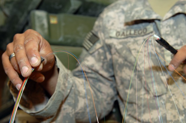"""BAGHDAD - Staff Sgt. Jose Gallego, of Bogota, Colombia, a computer systems repairer assigned to C Company, Division Special Troops Battalion, 1st Cavalry Division, prepares to splice a fiber optic cable at Joint Security Station Ur, here, June 19. """"When we come out and do this, we can actually see progress,"""" said Sgt. 1st Class Johnnie Pippin, of Liberty Center, Ohio, a communications chief. """"It feels good to provide something and actually see it work."""" According to Pippen, fiber optic cables use light signals to carry more information much faster than Ethernet cables."""