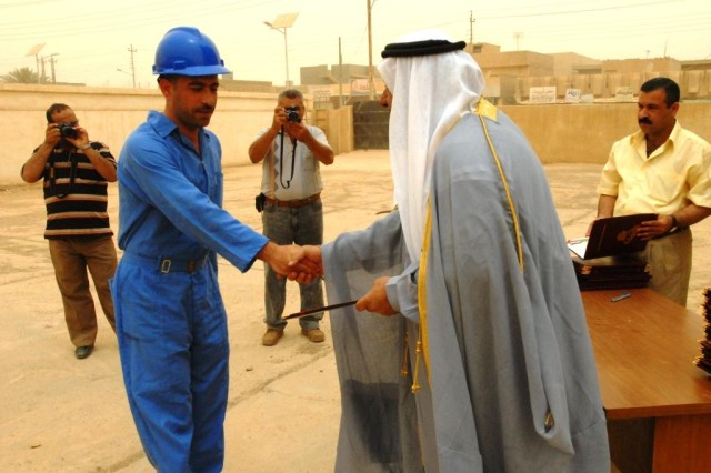 CAMP TAJI, Iraq -Sheikh Saed Jassim (right) presents a diploma to a new graduate of the Ministry of Electricity's Electrical Line Refurbishment Team class in Tarmiyah, June 18.  Twenty students graduated the six-week class which gave them skills needed to work on electrical infrastructure repairs in the Tarmiyah area for the ministry.