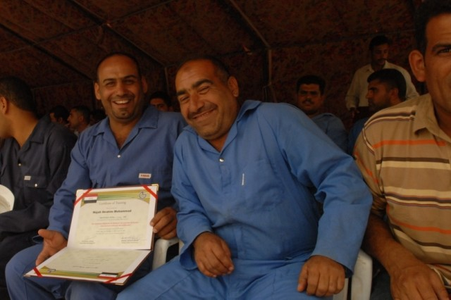 CAMP TAJI, Iraq - Two graduates of the Electrical Line Refurbishment Team course proudly show off their diplomas. Twenty students graduated the six-week class which gave them skills needed to work on electrical infrastructure repairs in the Tarmiyah area for the Ministry of Electricity.