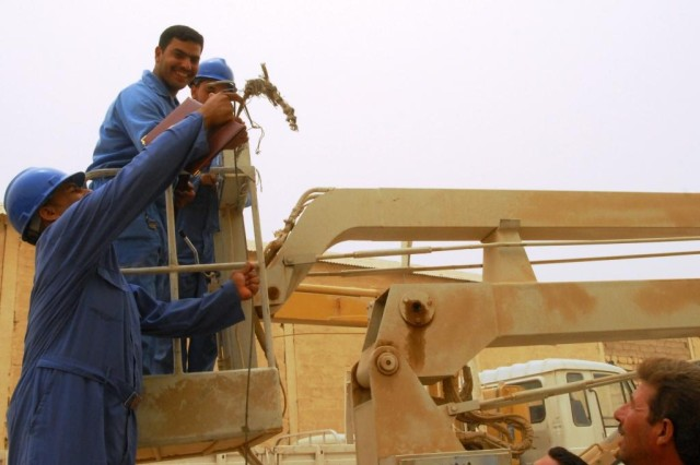 CAMP TAJI, Iraq - Students of the Electrical Line Refurbishment Team course in Tarmiyah demonstrate their new repair skills in a U.S.-funded bucket truck. Twenty students graduated the six-week class which gave them skills needed to work on electrical infrastructure repairs in the Tarmiyah area for the Ministry of Electricity.