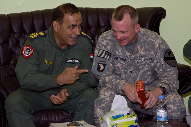 AL-TAJI AIRBASE, Iraq-In a gesture of appreciation, Brig. Gen. Nadhem Lafte al-AJwdi (left), of the Iraqi Air Force, commander of al-Taji Airfield, gives a gift to Col. Douglas Gabram (right), from Cleveland, Ohio, commander of the 1st Air Cavalry Brigade, 1st Cavalry Division, Multi-National Division-Baghdad, for his willingness to help the Iraqi AF and to improve relationships between the two, here, June 18.