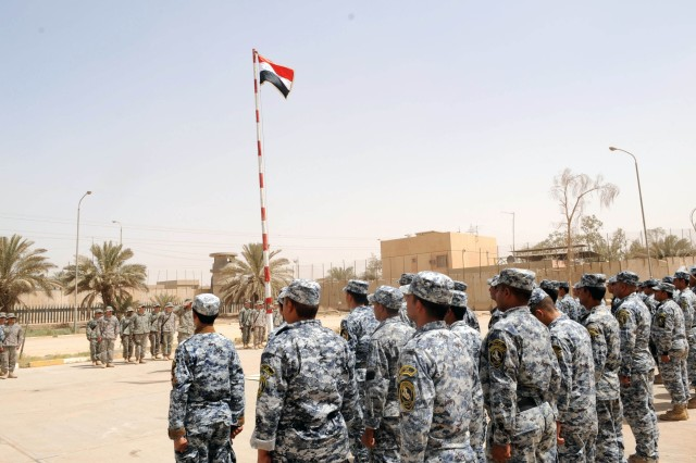 BAGHDAD - National Police officer assigned to the 8th NP Brigade, 2nd NP Division, and Paratroopers assigned to A Company, 2nd Battalion, 505th Parachute Infantry Regiment, 3rd Brigade Combat Team, 82nd Airborne Division, Multi-National Division-Baghdad, stand in formation during the transfer ceremony of Joint Security Station Oubaidy, June 20, in the 9 Nissan district of eastern Baghdad. The JSS was officially transferred to the Iraqi Security Forces during the ceremony.