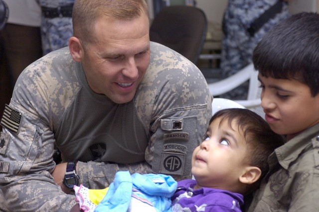 """BAGHDAD - Lt. Col. Louis Zeisman, of Fayetteville, N.C., greets a handicapped Iraqi boy during a humanitarian event, June 20, at Joint Security Station Beladiyat, located in the 9 Nissan district of eastern Baghdad. Paratroopers assigned to the 2nd Battalion, 505 Parachute Infantry Regiment, 3rd Brigade Combat Team, 82nd Airborne Division, Multi-National Division-Baghdad, partnered with National Police officers assigned to the 8th NP Bde., 2nd NP Div. to hand out more than 30 wheelchairs donated by the """"Wheelchairs for Iraqi Kids"""" organization. Each wheelchair is valued at $3,700 and is adjustable in order to adapt with growing children. Zeisman commands the 2nd Bn., 505 PIR, based out of Fort Bragg, N.C"""