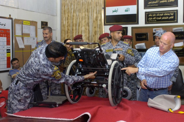 BAGHDAD - Brad Blauser (right), of Dallas, Texas, founder of Wheelchairs for Iraqi Kids, along with Iraq Brig. Gen. Ali Ibraheem Dabown, show parents of handicapped children how to adjust the wheelchairs they are about to receive during a humanitarian event, June 20, at Joint Security Station Beladiyat, located in the 9 Nissan district of eastern Baghdad. Blauser teamed up with Paratroopers assigned to the 2nd Battalion, 505 Parachute Infantry Regiment, 3rd Brigade Combat Team, 82nd Airborne Division, Multi-National Division-Baghdad and National Police officers assigned to the 8th NP Bde., 2nd NP Div. to hand out more than 30 wheelchairs donated by his organization. Blauser founded the organization in 2005 at the request of military officials after Soldiers in Mosul observed children drag themselves on the ground due to birth defects.