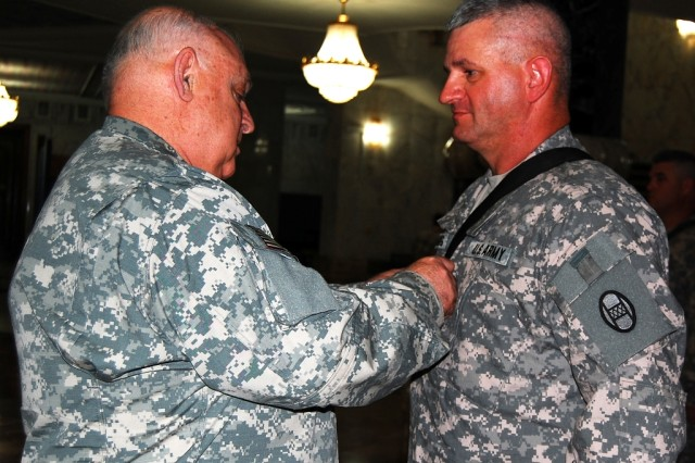 BAGHDAD- Maj. Gen. Allen Tackett (left), the West Virginia National Guard State Adjutant General, promotes 1st Sgt. Don Fleming after a reenlistment ceremony at Camp Victory Base Complex, June17.   Tackett re-capped the accomplishments of Fleming's career and expressed that he was proud to pin on his new rank.