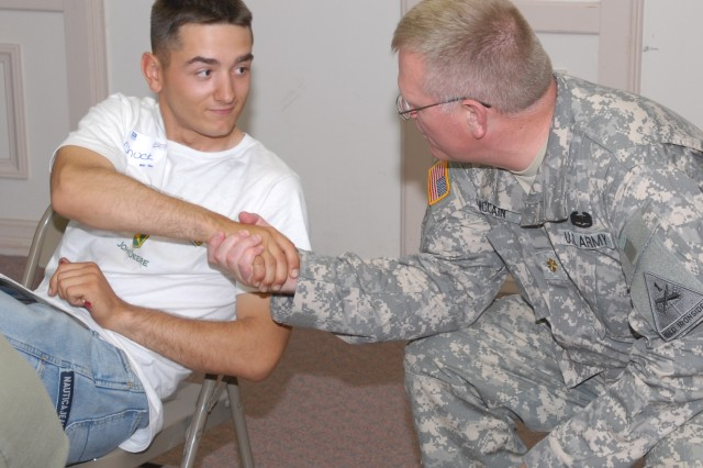 Chaplain  (Maj.) Henry McCain, 1st Brigade Combat Team, 1st Armored Division chaplain, greets a participant in a local military marriage seminar. The seminar included a question and answer segment that dealt with topics like explaining deployments to small children and positive activities to reconnect with your spouse. (Army Photo by Pfc. Jennifer Kennemer)