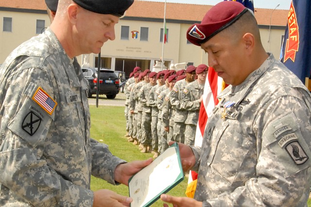 Having just fastened a Silver Star on the uniform of Staff Sgt. Conrad Begaye (right) from 2nd Battalion, 503rd Infantry Regiment, Maj. Gen. William B. Garrett III, commander of U.S. Army Africa, presents Begaye with an official citation during a ceremony on June 30, 2009. Begaye was awarded the Silver Star for his valorous actions during an enemy ambush Nov. 9, 2007, in the Nuristan Province of Afghanistan.