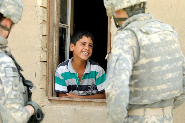 BAGHDAD -Soldiers of the 120th Combined Arms Battalion, 30th Heavy Brigade Combat Team, chat with a young boy outside his home, June 22. The 120th Soldiers conducted a census in the village nearest to Forward Operating Base Mahmudiyah, taking time to talk to everyone in the village.