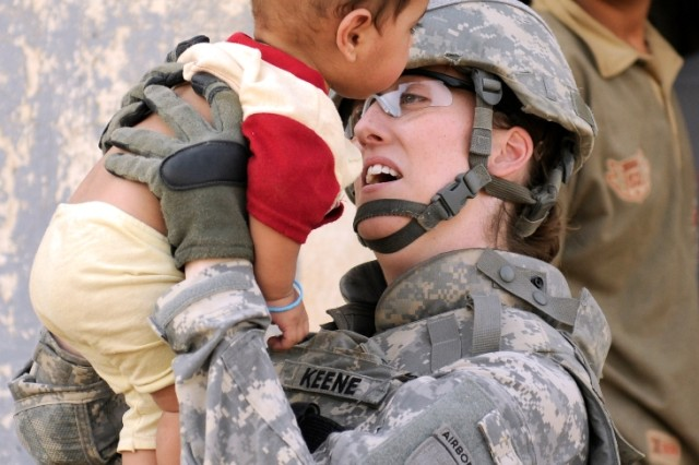 BAGHDAD - Sgt. Elisabeth Keene, attached to the 120th Combined Arms Battalion, 30th Heavy Brigade Combat Team, plays with a little boy outside of Forward Operating Base Mahmudiyah, June 22. Keene, of Fairfax, Va., is part of a group of Soldiers who went to the village on the other side of the FOB wall to conduct a census in the area.