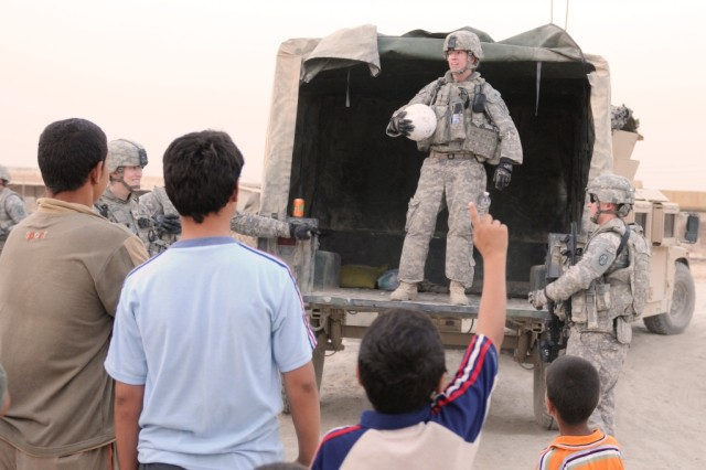 BAGHDAD- Capt. Sara Woods (standing in humvee), of Janesville, Minn., prepares to throw a soccer ball to a group of children, June 22, in a village just outside of Forward Operating Base Mahmudiyah. Woods, part of Civil Affairs Team 31, 120th Combined Arms Battalion, 30th Heavy Brigade Combat Team, was part of a group of Soldiers conducting a census in a village near the base.