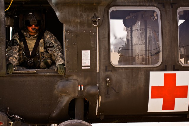"CAMP TAJI, Iraq-During the initial run up, before taking over the day's mission, Sgt. Randy Sanchez, from Rio Grande City, Texas, a flight medic in C Company ""Medevac,"" 2nd Battalion, 1st Air Cavarly Brigade, 1st Cavarly Division, sits in a UH-60 Black Hawk helicopter while the aviators conduct daily checks on the aircraft, June 22. The initial run-ups are conducted to save the medevac crew time if they have an emergency call."