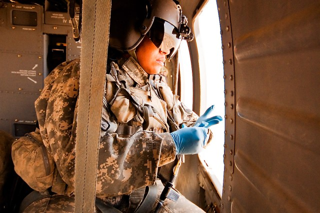"""TAJI, Iraq-Watching vigilantly out of the window for the landing site, Sgt. Karen Henson, from Fredericksburg, Va., a flight medic in Company C """"Medevac,"""" 2nd Battalion, 1st Air Cavarly Brigade, 1st Cavarly Division, puts on her surgical gloves as the UH-60 Black Hawk helicopter approaches it's destination,June 22.  The medevacs were called to transport a Soldier wounded by a grenade attack."""