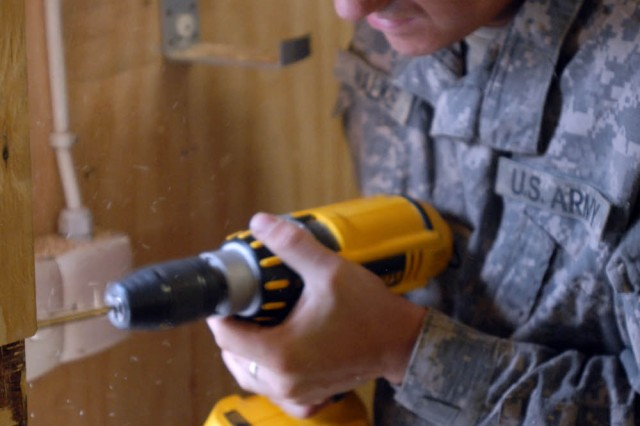 "BAGHDAD -Kokomo, Ind. native, Pfc. Nathan Walker, a tanker for C Company, 2nd ""Lancer"" Battalion, 5th Cavalry Regiment,  1st ""Ironhorse"" Brigade Combat Team, 1st Cavalry Division, works on the door to the new Morale, Welfare and Recreation building, June 23."