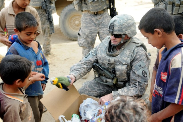 MAHMUDIYAH, Iraq - Command Sgt. Maj. Russell Prince, 120th Combined Arms Battalion, 30th Heavy Brigade Combat Team, of Sneads Ferry, N.C., hands out toys to children on a dairy farm south of Baghdad, June 23.  Soldiers with the 120th Combined Arms Battalion, 30th Heavy Brigade Combat Team, and a family of Iraqi dairy farmers are spearheading a pilot program designed to increase milk and cheese production in the Mahmudiyah area.