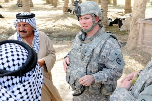 MAHMUDIYAH, Iraq - Lt. Col. Jack Mellott, commander of the 120th Combined Arms Battalion, 30th Heavy Brigade Combat Team, talks with owners of a dairy farm south of Baghdad, June 23.