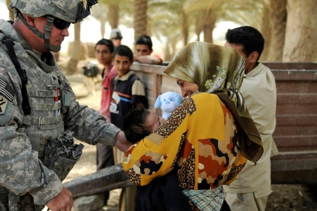 090623-A-8124P-015 MAHMUDIYAH, Iraq - Sgt.Kenneth Steinbronn, 120th Combined Arms Battalion, 30th Heavy Brigade Combat Team, hands a stuffed toy to an infant at a dairy farm near Mahmudiyah, June 23.  Steinbronn, of Dorchester, N.C., and other members of the North Carolina Army National Guard brigade are working with a family of Iraqi dairy farmers to spearhead a pilot program to increase milk and cheese production in the Mahmudiyah area.