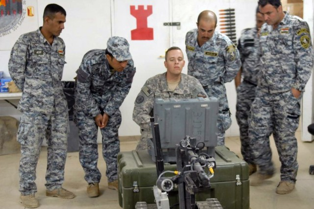 BAGHDAD - Staff Sgt. Joseph Ray (center), of Baton Rouge, La., gives instruction to Iraqi 2nd NP officers on how to maneuver the Talon robot, used to detect deadly IEDs. The class was part of a three-day course on route clearance taught at the 225th Engineer Brigade's Task Force Iron Claw Academy at Camp Liberty, June 24.