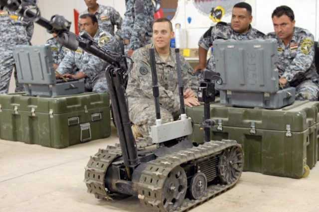 BAGHDAD - Staff Sgt. Joseph Ray (center), of Baton Rouge, La., watches as his students, 2nd National Police officers, operate the Talon robot, June 24. The class was part of a three-day course on route clearance taught at the 225th Engineer Brigade's Task Force Iron Claw Academy at Camp Liberty.