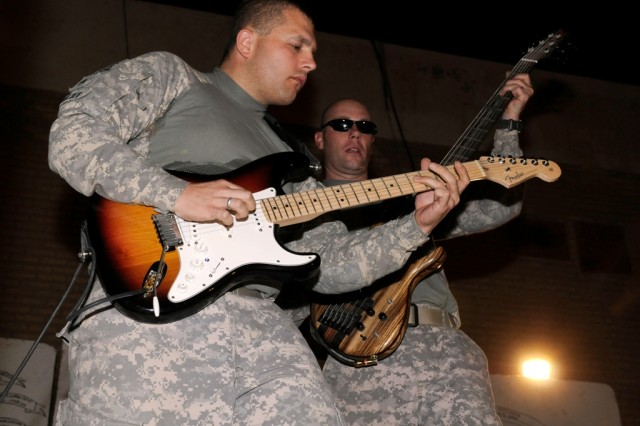 MAHMUDIYAH, Iraq - Guitarist Sgt. Jason Smelser (left), of Killeen, Texas, and bassist Staff Sgt. Dennis Milne, of Rockford, Ill., with the 1st Calvary Division Army Rock Band, jam at Forward Operating Base Mahmudiyah June 23. The band, known as G.O. 1 Underground, plays for Soldiers in Iraq.